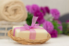 Pedazo grande de jabón beige en el busket, arco púrpura del witn, flores en b Foto de archivo libre de regalías
