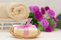 Pedazo grande de jabón beige en el busket, arco púrpura del witn, flores en b Imagenes de archivo