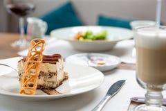 Pedazo hermoso de tiramisu delicioso con los microprocesadores del caramelo y de latte en un café fotos de archivo