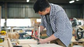 Pedazo masculino de la fijación del carpintero de madera en la mesa de trabajo usando los instrumentos especiales almacen de metraje de vídeo