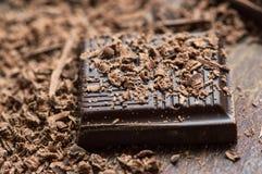 Pedazo oscuro del chocolate con el fondo Fotografía de archivo