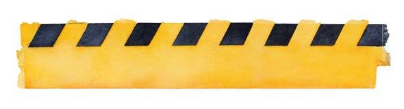 Pedazo sucio amarillo de la cinta del color de agua con las líneas frontera diagonales negras foto de archivo