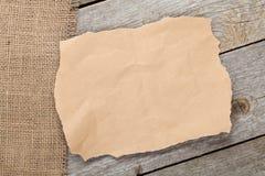 Pedazo y arpillera de papel viejos en fondo texturizado de madera Fotos de archivo