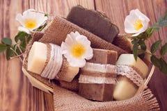 Pedazos adornados de diverso jabón seco en una cesta con las rosas Fotos de archivo libres de regalías