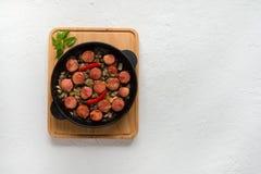 Pedazos apetitosos de salchicha frita con las cebollas en una cacerola de la porción Visión superior foto de archivo