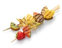 Pedazos asados a la parrilla de la fruta en el pincho fotos de archivo