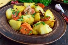 Pedazos cocidos de la patata de, ` en un rústico, ` de la zanahoria con las hierbas en un cuenco de la arcilla en fondo de madera imagenes de archivo