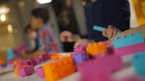Pedazos constructivos coloridos del juego para los niños en la tabla metrajes