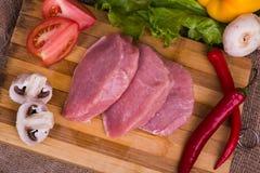Pedazos cortados de carne cruda para la barbacoa con los tomates de las verduras frescas, lechuga en superficie de madera Visión  imágenes de archivo libres de regalías
