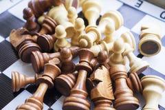 Pedazos de ajedrez dispersados en el tablero de ajedrez Fotos de archivo libres de regalías