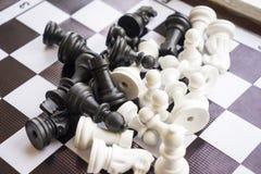 Pedazos de ajedrez dispersados en el tablero de ajedrez Imágenes de archivo libres de regalías