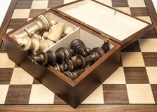 Pedazos de ajedrez en caja de almacenamiento abierta en tablero de ajedrez Imágenes de archivo libres de regalías