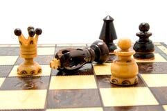 Pedazos de ajedrez en el tablero de ajedrez con el rey caido Foto de archivo libre de regalías