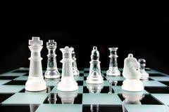 Pedazos de ajedrez en una tarjeta de cristal fotografía de archivo
