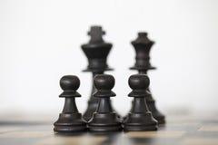 Pedazos de ajedrez negros del rey y de la reina con los empeños Fotografía de archivo libre de regalías
