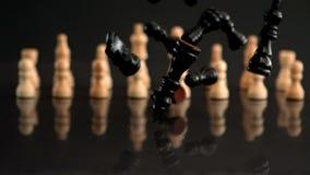 Pedazos de ajedrez negros que caen en fondo negro con los pedazos blancos almacen de video
