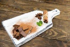 Pedazos de anís del chocolate, del canela, de la menta y de estrella en una tabla de cortar foto de archivo libre de regalías