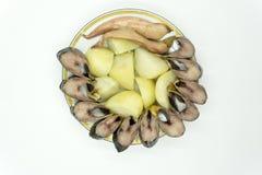 Pedazos de arenques con las cebollas, los pepinillos y las patatas hervidas imagen de archivo