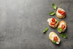 Pedazos de baguette con el queso cremoso y los tomates sabrosos en la tabla gris, endecha plana imágenes de archivo libres de regalías