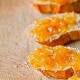 Pedazos de baguette con la mermelada anaranjada Fotografía de archivo libre de regalías