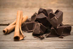 Pedazos de barra de chocolate con canela en fondo de madera imagen de archivo libre de regalías
