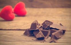 Pedazos de barra de chocolate con dos corazones fotografía de archivo