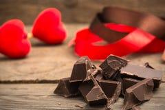 Pedazos de barra de chocolate con la cinta roja y marrón foto de archivo libre de regalías