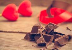 Pedazos de barra de chocolate con la cinta roja y marrón foto de archivo