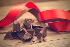 Pedazos de barra de chocolate con la cinta roja y marrón en la parte posterior de madera foto de archivo libre de regalías