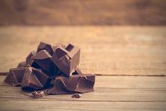 Pedazos de barra de chocolate en fondo de madera fotografía de archivo