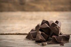 Pedazos de barra de chocolate en fondo de madera imagen de archivo libre de regalías