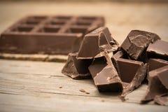 Pedazos de barra de chocolate en fondo de madera foto de archivo