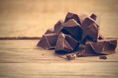 Pedazos de barra de chocolate en fondo de madera fotos de archivo libres de regalías