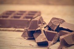 Pedazos de barra de chocolate en fondo de madera fotografía de archivo libre de regalías