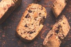 Pedazos de biscotti italiano en un fondo negro con el polvo de cacao Fotografía de archivo