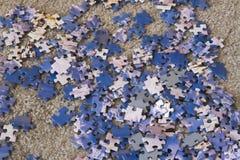 Pedazos de bloques del rompecabezas en la alfombra Fotos de archivo libres de regalías