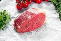 Pedazos de carne fresca, de losa de la carne de vaca, adornadas con verdes y verduras Foto de archivo libre de regalías