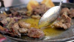 Pedazos de carne que vierten con aceite usando la cuchara en un sartén, opinión del primer almacen de video
