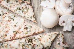 Pedazos de champiñones de la pizza y de las setas en un fondo de madera ligero Fotografía de archivo