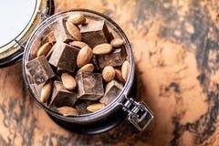 Pedazos de chocolate amargo oscuro con las almendras del cacao y de las nueces en fondo de madera Concepto de ingredientes de la  foto de archivo libre de regalías