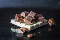 Pedazos de chocolate con leche con las almendras y las tejas del chocolate blanco con las avellanas en un viejo fondo brillante o Foto de archivo