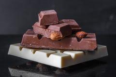 Pedazos de chocolate con leche con las almendras y las tejas del chocolate blanco con las avellanas en un viejo fondo brillante o Fotografía de archivo libre de regalías