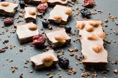 Pedazos de chocolate oscuro con las nueces y las frutas secadas en un fondo de migas imagen de archivo