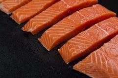 Pedazos de color salmón frescos en fondo del negro oscuro Fotografía de archivo