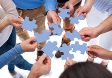 Pedazos de conexión del rompecabezas del grupo de personas Imagen de archivo libre de regalías