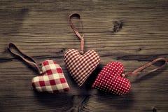 3 pedazos de corazones de la tela, lunares, tela escocesa, en el fondo de madera Fotografía de archivo