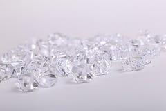 Pedazos de cristal dispersados del diamante en un fondo blanco Imagen de archivo