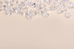 Pedazos de cristal dispersados del diamante en un fondo poner crema Fotografía de archivo libre de regalías