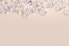 Pedazos de cristal dispersados del diamante en un fondo poner crema Fotos de archivo libres de regalías