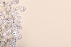 Pedazos de cristal dispersados del diamante en un fondo poner crema Foto de archivo libre de regalías